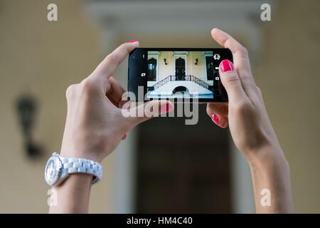 Photos sites architecturaux, sur le téléphone mobile. Women's Hands holding manucure rouge avec un téléphone à écran Banque D'Images