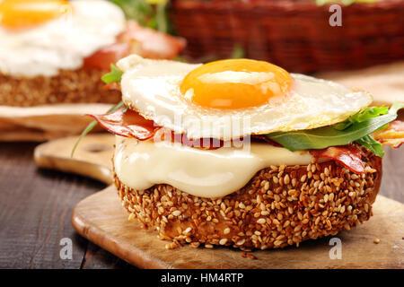 Avec du fromage sandwich bacon et œuf frit sur fond de bois Banque D'Images