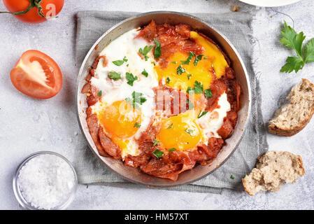 Oeufs au plat avec les tomates et le bacon dans une poêle à frire, vue du dessus, Close up Banque D'Images