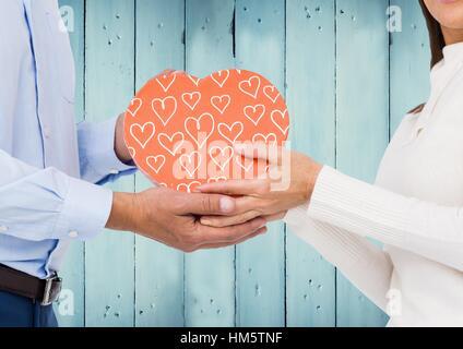 Image composite du couple holding coeur rose bleue contre les panneaux de bois Banque D'Images