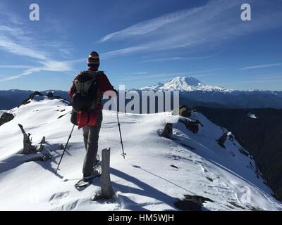 Vue arrière de l'homme marchant sur la neige champs couvert contre le ciel Banque D'Images