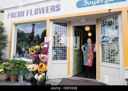 Portrait of female florist standing in doorway of flower shop