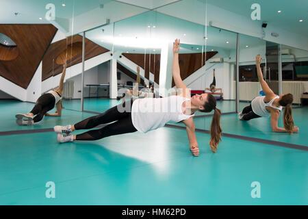 Toute la longueur de belle jeune femme avec des corps parfaits dans les vêtements de sport faisant planche latérale Banque D'Images