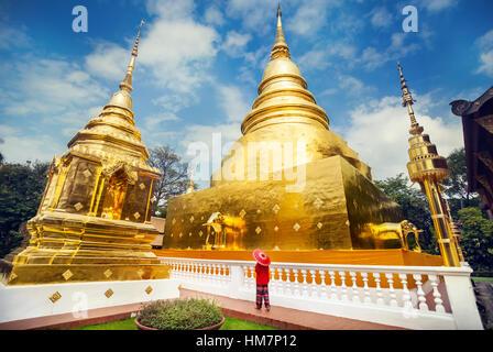 Tourisme Femme avec parapluie traditionnel Thaï rouge près de stupa doré au temple Wat Phra Singh de Chiang Mai, Banque D'Images