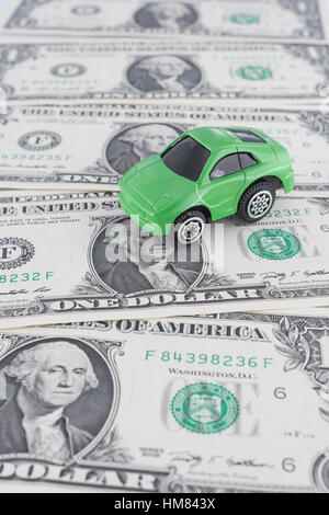 Petite voiture jouet vert sur nous 1 / 1 $ Dollar bills. Comme métaphore pour le coût de l'automobile et de l'essence Banque D'Images