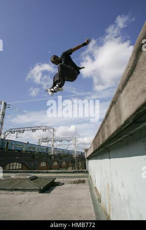 Un athlète factory ♡ lovely fairies ♡ pascal Alexandra parkour entre les niveaux de saut sur un toit. Un train passe Banque D'Images