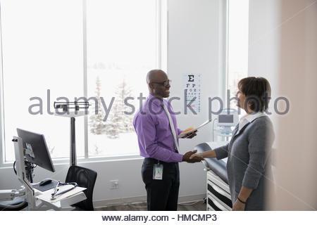 Doctor shaking hands with female patient dans la salle d'examen clinique Banque D'Images