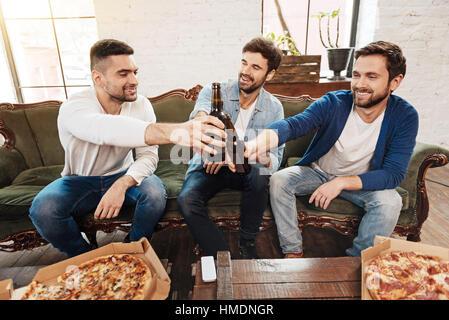 Les hommes joyeux positif pour les bouteilles de bière de pain grillé Banque D'Images