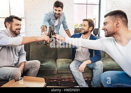 Les hommes joyeux tintement des bouteilles Banque D'Images