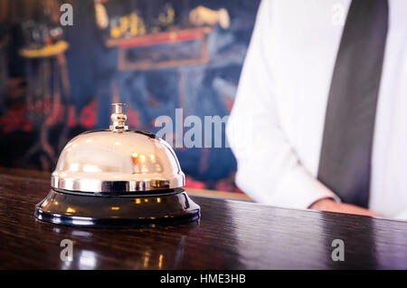 Service de réception de l'hôtel bell avec concierge accueillant dans l'arrière-plan Banque D'Images