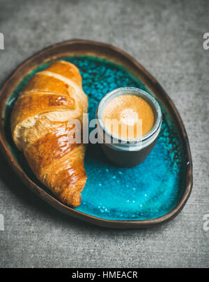 Tasse de café expresso et un croissant dans le bac en céramique bleu turquoise sur fond de béton gris, selective Banque D'Images