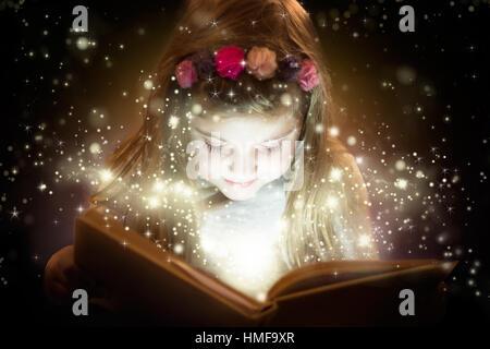 Belle petite fille lecture livre de magie, fantaisie concept Banque D'Images