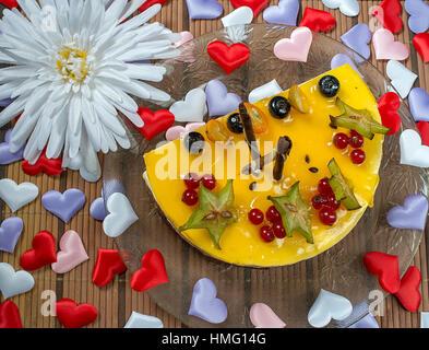 Cheesecake aux fruits rouges coeurs rouges sur la plaque Banque D'Images