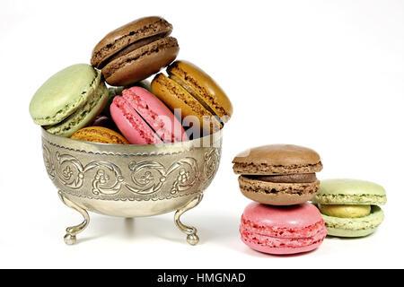 Macarons colorés dans un bol en argent isolé sur fond blanc Banque D'Images
