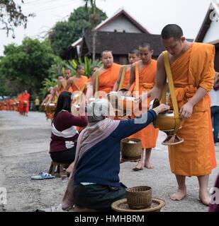 Les moines et les donateurs, tôt le matin, Procession d'aumône, Luang Prabang, Laos Banque D'Images