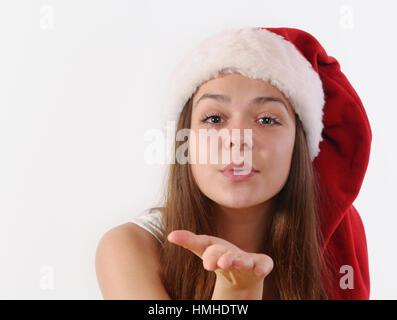 Portrait of beautiful girl in Santa hat soufflant un baiser à l'appareil photo, vacances de Noël, happy holiday Banque D'Images