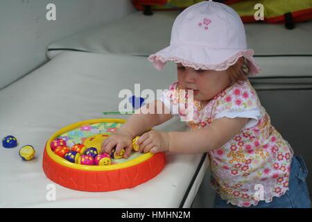 Petite fille toddler bébé enfant kid portant un t-shirt chapeau bonnet porté de jouer à un jeu avec des pièces d'apprentissage Banque D'Images