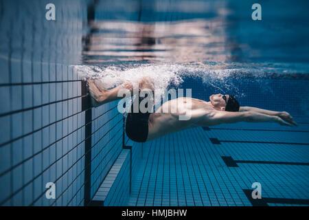 Coup de jeune homme fit retourner sous l'eau. Nageur Pro en action à l'intérieur de la piscine. Banque D'Images