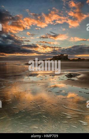 Lever du soleil sur le château de Bamburgh Northumberland, Banque D'Images