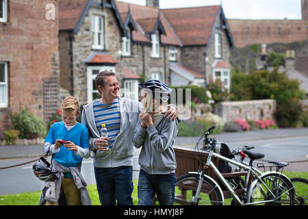 Père et Fils s'arrêtant dans un village au milieu de leur promenade en vélo pour prendre un verre. Ils portent des Banque D'Images