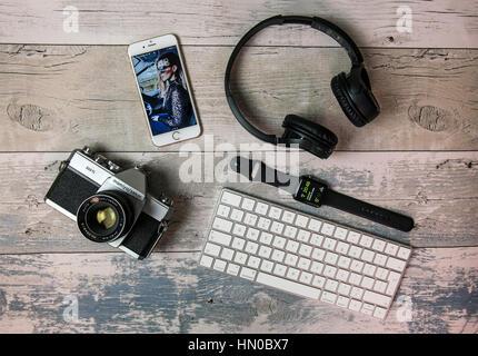 Mise à plat avec de vieux film SLR appareil photo, iPhone, Apple, clavier et casque watch Banque D'Images