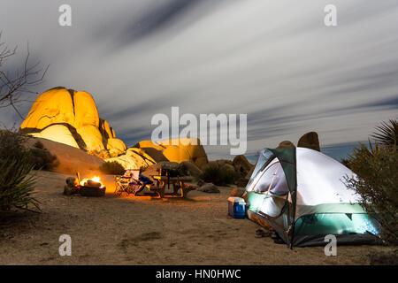 Une tente est assis à côté d'un feu de camp dans la nuit dans un camping du parc national de Joshua Tree. Banque D'Images