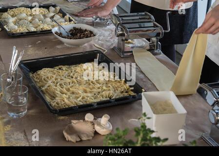 Personne l'exploitation d'une machine à pâtes avec des pâtes et autres produits d'épicerie sur la table Banque D'Images
