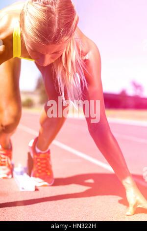 Athlète féminin prêt à fonctionner sur une piste de course sur une journée ensoleillée Banque D'Images