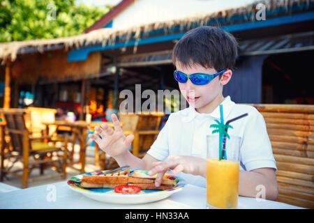 Cute little boy having lunch à l'extérieur restaurant Banque D'Images