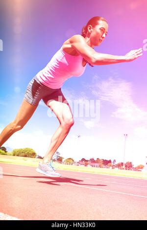 Athlète féminin s'exécutant sur une piste de course aux beaux jours Banque D'Images