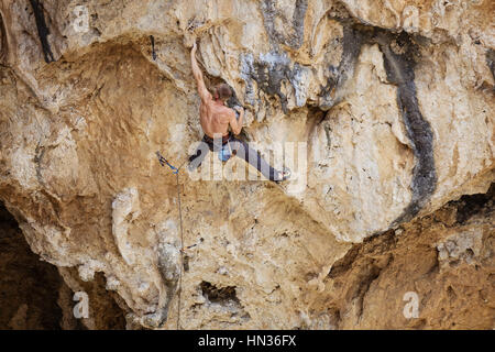 Rock climber sur route difficile sur falaise Banque D'Images