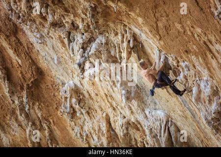 Assez rock climber resting avant d'atteindre la poignée. Route difficile sur falaise en surplomb. Banque D'Images