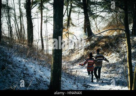 Couple holding hands courir loin de la forêt en hiver Banque D'Images