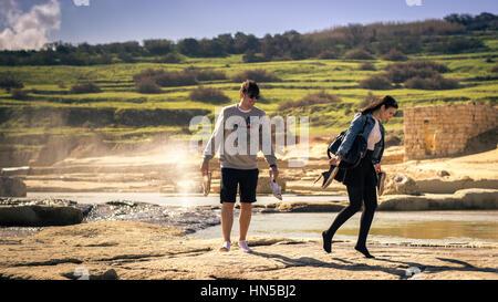 Un beau jeune couple en train de marcher sur la mer ayant leur place dans leur main. L'emplacement est à Malte au Banque D'Images