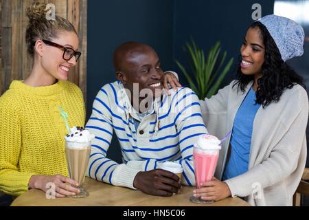 Happy friends interagir tout en ayant le café et des milk-shakes dans café Banque D'Images