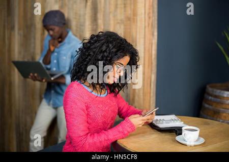 Femme assise à la table et à l'aide de téléphone mobile tout en ayant un café dans café