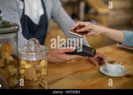 Femme de payer bill par smartphone à l'aide de la technologie NFC dans cafe Banque D'Images