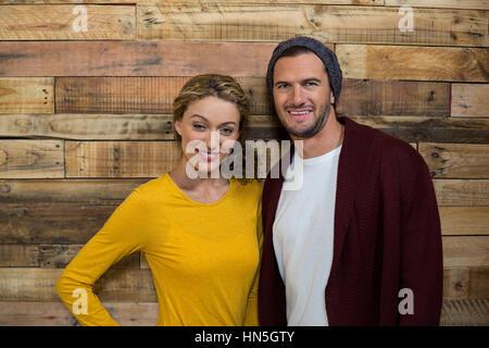 Portrait of smiling couple debout contre la paroi en bois de café Banque D'Images