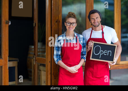 Portrait of smiling waitress and waiter standing with open sign board hors café Banque D'Images