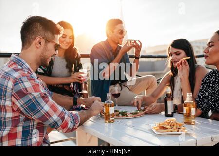 Groupe de jeunes gens assis autour et manger des pizzas. Les amis à faire la fête et manger des pizzas. Banque D'Images