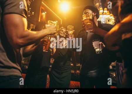 Groupe d'amis ayant des boissons au bar ensemble. Les jeunes à profiter de nuit avec des cocktails. Banque D'Images