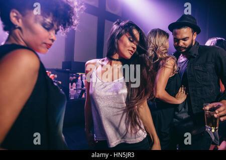 Young woman dancing at party avec des amis à proximité. Groupe de jeunes s'amusant à la discothèque.