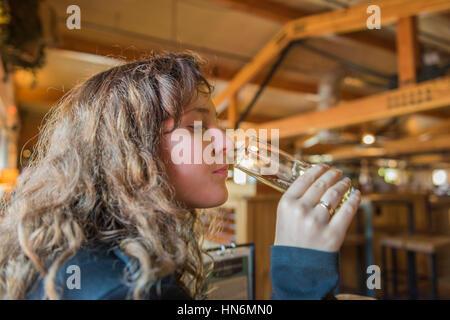 Jeune femme girl holding et dégustation de bière pâle lumière en verre bar bavarois rustique en bois Banque D'Images