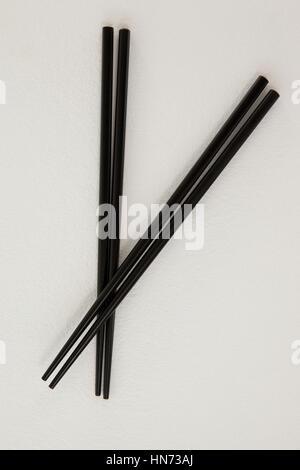 Deux Paire de baguettes noires contre fond blanc Banque D'Images