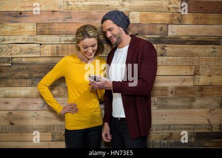 Couple using mobile phone in café contre le mur en bois Banque D'Images