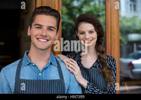 Portrait of smiling waiter et serveuse debout à l'extérieur du cafe Banque D'Images