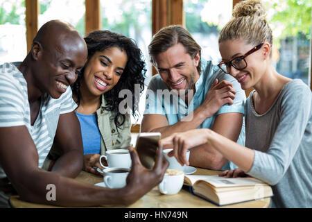 Groupe d'amis à l'aide de mobile tout en ayant tasse de café dans la région de café Banque D'Images