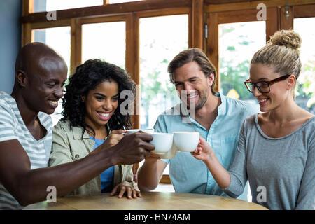 Groupe d'happy friends toasting tasse de café dans la région de café Banque D'Images