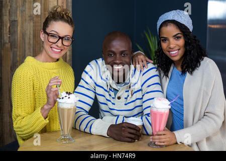 Portrait of happy friends having coffee et des milk-shakes dans café Banque D'Images