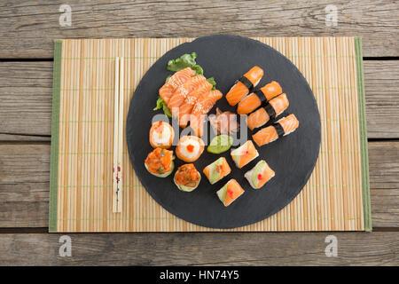 Plateau en ardoise d'un assortiment de sushi conservés sur tapis contre fond de bois Banque D'Images